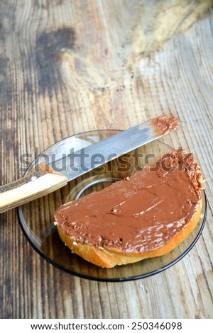 A toast with chocolate spread all over it with a knife on wooden table