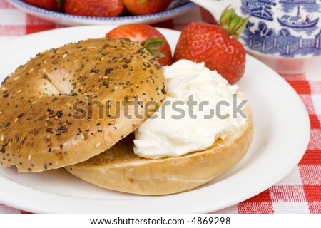 A toasted bagel with cream cheese for breakfast. Fresh strawberries on the side. Shallow dof.