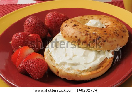 A toasted onion bagel with cream cheese and ripe strawberries - stock photo