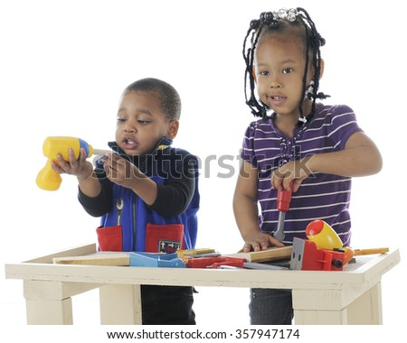 A toddler brother and preschool sister playing together with the toy tools on a workbench.  Taken on a white background. - stock photo