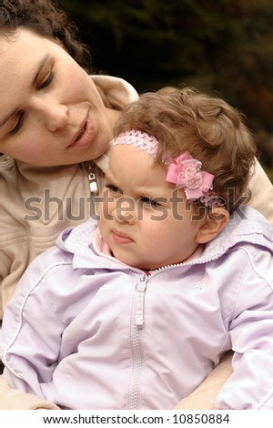 A toddler daughter listens attentively to her mother - stock photo