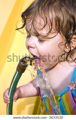 a toddler drinking water from a garden hose - stock photo