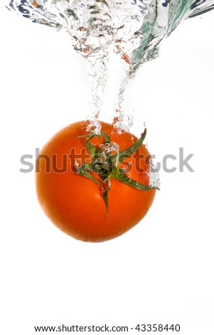 A tomato falling into clear water