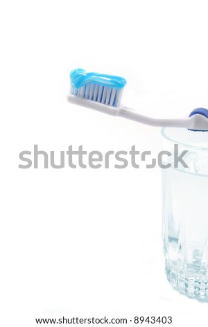 A toothbrush with blue toothpaste on glass of water