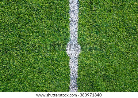 A top down angle view of white line on a green soccer field. - stock photo