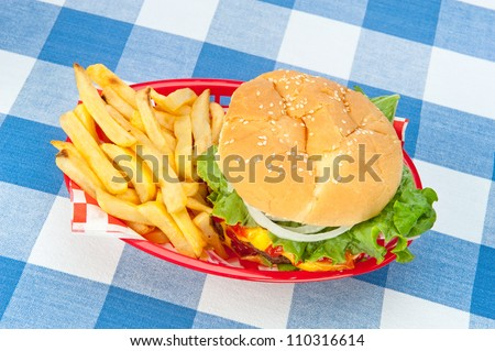 A top down view of a hamburger with fries in a red basket on a picnic tablecloth. - stock photo