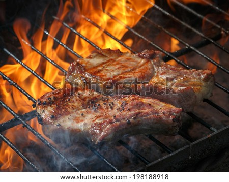 A top sirloin steak flame broiled on a barbecue, shallow depth of field - stock photo