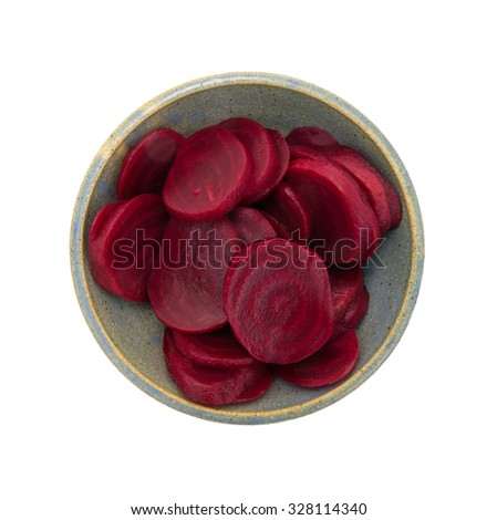 A top view of a colorful bowl of sliced beets in a gray ceramic bowl on a white background. - stock photo