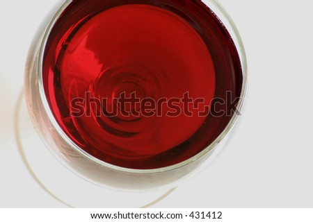 A top view of a glass of red wine, air bubbles in the wine are also visible.