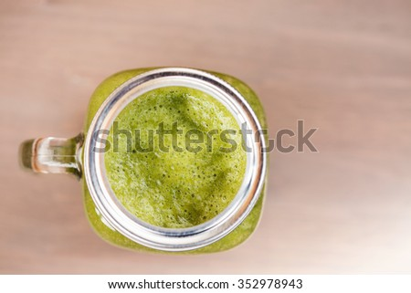 A top view of a green smoothie in a mason jar on wooden background