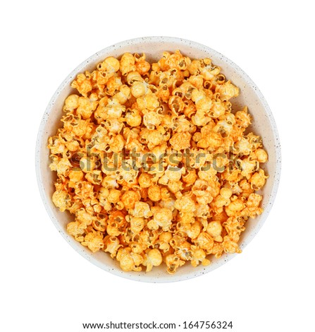 A top view of a  large bowl of cheddar cheese popcorn with a hot sauce flavor on white. - stock photo