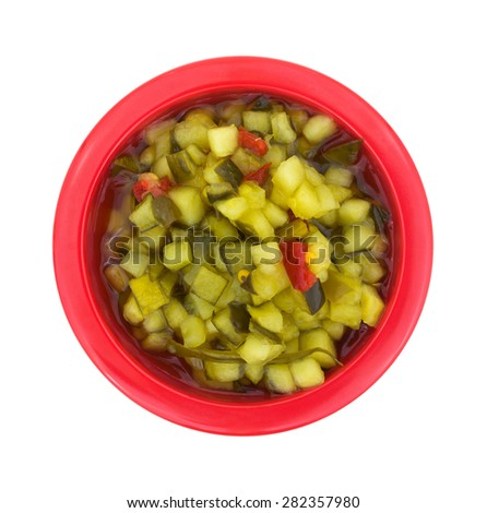 A top view of a red bowl filled with finely chopped sweet relish. - stock photo
