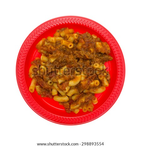 A top view of a red dish filled with a generic brand of macaroni and cheese on a white background. - stock photo