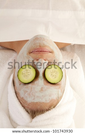 A top view of a woman in the spa with cucumbers on her eyes. - stock photo