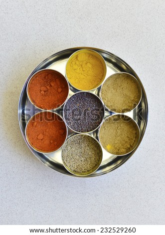 A top  view of an indian spice box with multiple containers. - stock photo