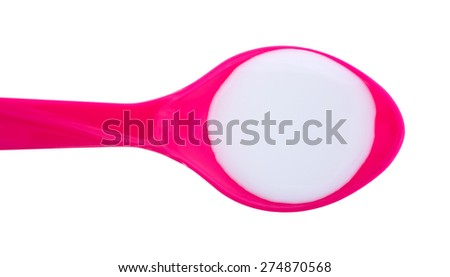 A top view of liquid antacid on a pink spoon on a white background. - stock photo