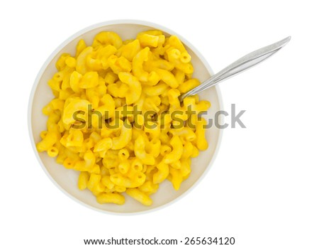 A top view of macaroni and cheese on a plate with spoon. - stock photo
