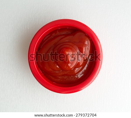A top view of red bowl filled with ketchup isolated on a white cutting board. - stock photo