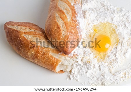 A torn baguette with flour and a cracked egg. - stock photo