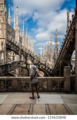 A tourist admires the spiers of Milan Cathedral Duomo. Milan, Italy