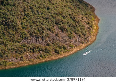 A tourist boat navigating around one of the center islands at the volcanic crater and lake of Cuicocha - stock photo