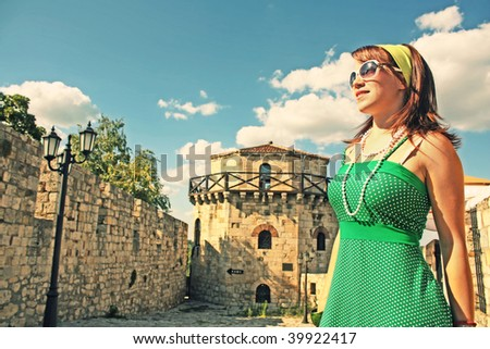 A tourist girl in a green dress at the Belgrade old fortress in Kalemegdan. - stock photo