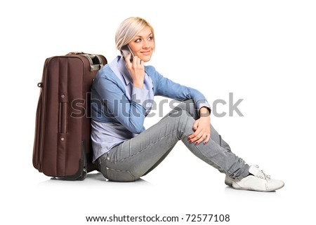 A tourist girl seated next to a suitcase talking on mobile phone isolated on white background