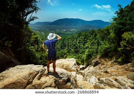 A tourist is standing on the top of the mountain and looking at the picturesque landscape. - stock photo