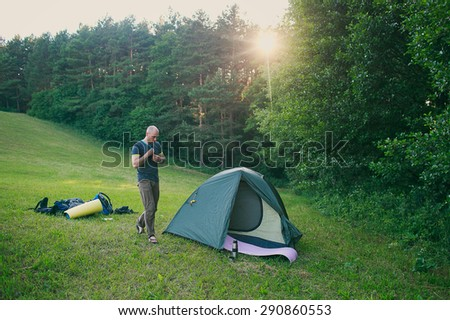 a tourist is walking to a tent in the forest