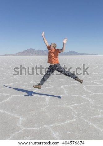 A tourist jumps in the barren landscape of the Salt Flats in Utah - stock photo