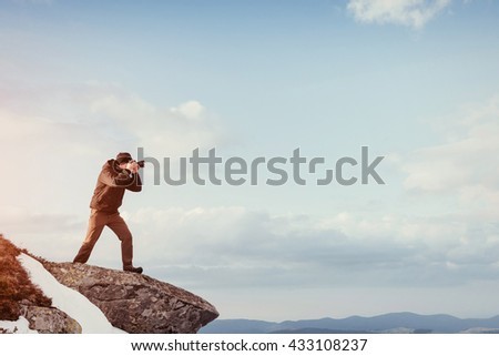 A tourist looks at the landscape. Photographer on top of mountain. Spring landscape. Carpathians, Ukraine, Europe