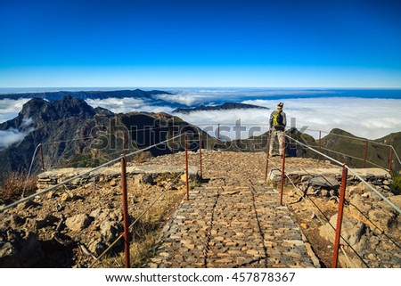 a tourist man standing on the highest point of Madeira - Pico Ruivo, looking down to the mountains