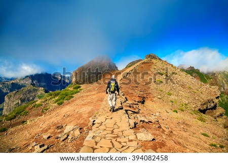 a tourist man walking along the footpath at Pico do Arieiro, Madeira, Portugal - stock photo