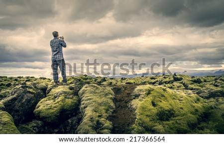 A tourist snapping a photo of moss covered lava rocks in Vatnajokull National Park, Iceland - stock photo