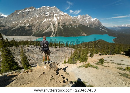 a tourist standing on a cliff looking down to Peyto Lake in Alberta,Canada - stock photo