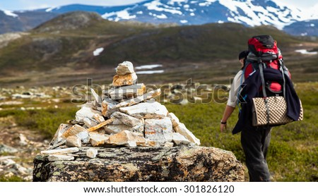 A tourist with a large backpack is passing a pyramid-shaped milestone on a mountain trail. The path leads trough grass and small bushes towards high mountains, partially covered with snow - stock photo