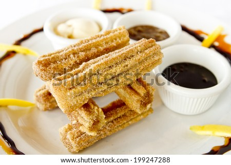A tower of churros with sauces. - stock photo