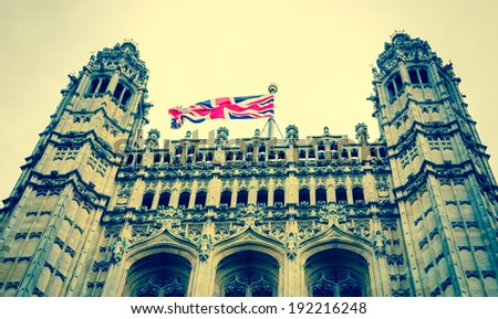 A tower of  House of Parliament with British flag. (London, UK). Aged photo. - stock photo