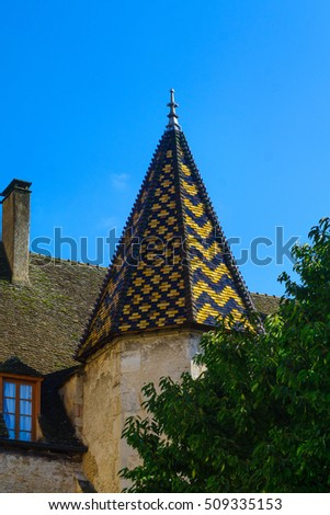 A tower with typical colored patterned roof, part of the Notre-Dame church, in Beaune, Burgundy, France