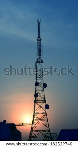 A towering radio towers under the setting sun