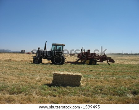 A tractor bailing hay - stock photo