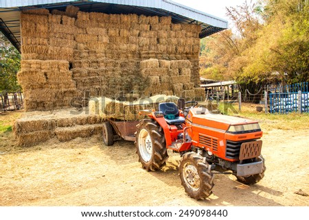 A tractor in a hay warehouse - stock photo