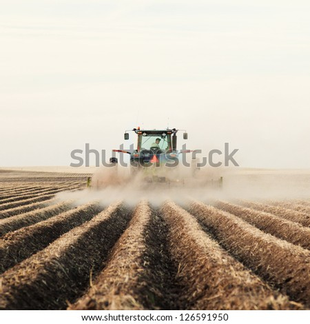 A tractor planting a potato crop on the prairies. - stock photo