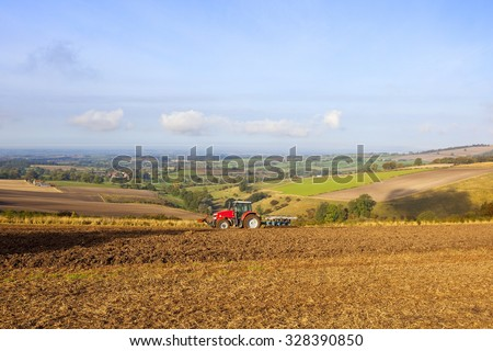A tractor plowing a hillside field on the Yorkshire wolds in Autumn. - stock photo