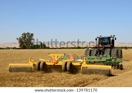 A tractor pulls a disc harrow system implement to smooth over a dirt field in preparation for planting in central California - stock photo