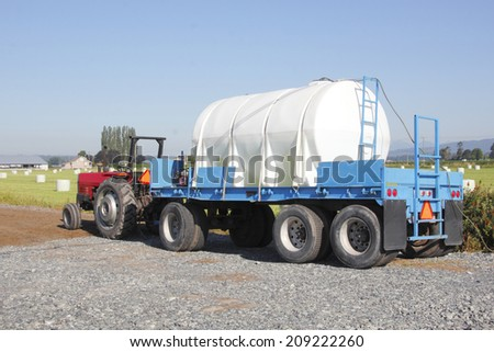 A tractor  pulls a tank used for distributing chemicals/Agriculture Chemical Tank/Tractor is used to pull a tank used for chemicals that kill fungus and insects that harm crops. - stock photo