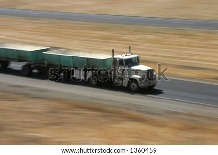 A tractor-trailer hauls some stuff down the highway. - stock photo