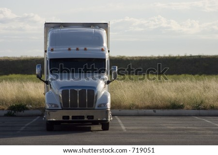 A tractor-trailer truck in a parking lot. - stock photo