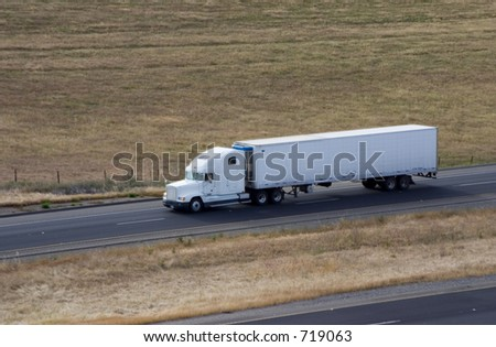 A tractor-trailer truck in cruising along the highway. - stock photo