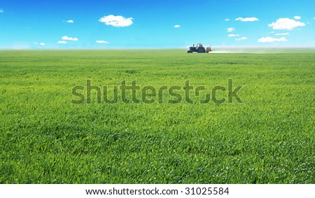a tractor working in a field - stock photo